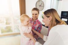 Der Babysitter trifft die Mutter der Kinder und hält das Baby in ihren Armen Das ältere Mädchen umarmt Mutter stockfoto