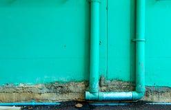 Der Backsteinmauer wird grün und das begonnene Wasser gemalt Lizenzfreies Stockbild
