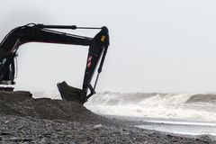Der Bagger funktioniert mit einem Eimer, der von den Steinen auf Küste im stürmischen Wetter voll ist Stockfoto