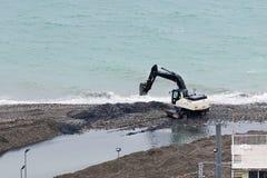 Der Bagger funktioniert, um den Kanal für die Entladung des Abwassers in das Meer zu erweitern Stockfotografie