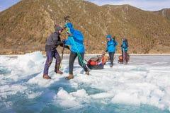Der Baikalsee, Russland - 24. März 2016: Die Männer schleppten das Eis SL Stockfotos