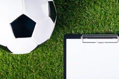 Der Ball für das Spielen des Fußballs liegt auf einem grünen Rasen, da ein Hintergrund und dort ein Platz für das Notieren des Er Lizenzfreie Stockbilder