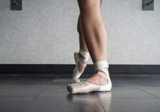 Der Balletttänzer, der ihr pointe vorführt, beschuht Stellung in der klassischen Position stockbilder