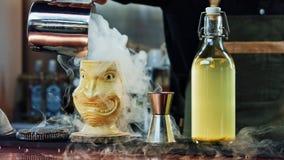 Der Barmixer gießt Dampf in einem Tiki-Glas Stockfotos
