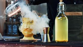 Der Barmixer gießt Dampf in einem Tiki-Glas Stockfotografie
