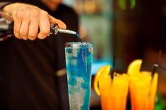 Der Barmixer gießt den Alkohol in ein exotisches Cocktail Lizenzfreie Stockfotografie
