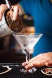 Der Barmixer gießt ein Getränk auf einer Nahaufnahme des kalten Glases Lizenzfreie Stockbilder