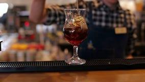 Der Barmixer gießt einen Koks in ein leeres Glas Eis in der Stange stock video