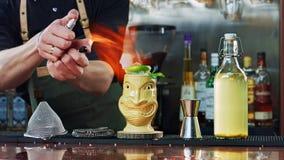 Der Barmixer stellt das Cocktail auf Feuer ein Stockbild