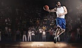 Der Basketball-Spieler springend mit Ball auf Stadion in den Lichtern Stockfotografie