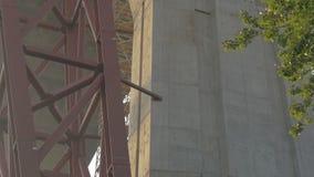 Der Bau der Straßenbrücke Die Ansicht von unterhalb über einen enormen Kran, uhd stock video