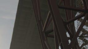 Der Bau der Straßenbrücke Die Ansicht von unterhalb über einen enormen Kran, uhd stock footage