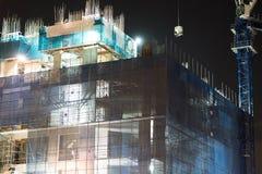 Der Bau hat sich vor gefährlichen SchrottBaumaterialien durch Gewächshausschattierungsnetz geschützt Stockbilder