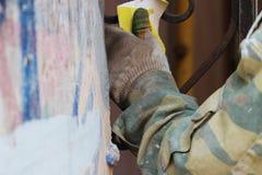 Der Bauarbeiter säubert das rostige alte Gitter am Bogen des alten Hauses in St Petersburg mit Sandpapier Lizenzfreies Stockbild