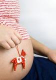 Der Bauch der schwangeren Frau mit einem Pferdespielzeug Lizenzfreie Stockfotografie