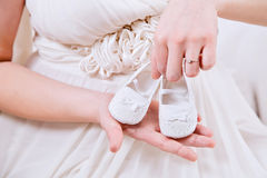 Der Bauch der schwangeren Frau mit weißen Beuten Stockbilder