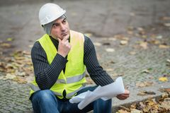 Der Bauingenieur, der ein schützendes weißes Sturzhelmrevisionsamt trägt, entwirft auf Baustelle Selektiver Fokus stockfoto