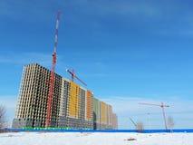 Der Baukran und das Gebäude gegen den blauen Himmel Lizenzfreies Stockfoto