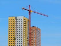 Der Baukran und das Gebäude gegen den blauen Himmel Stockbilder