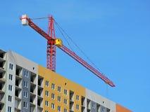 Der Baukran und das Gebäude gegen den blauen Himmel Lizenzfreie Stockfotografie