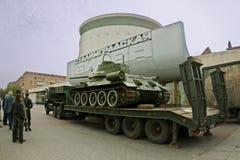 Der Behälter T-34 wird auf die Selbstplattform auf dem Hintergrund des Panoramamuseum ` Kampfes von Stalingrad-` für Transport ge Lizenzfreie Stockfotografie