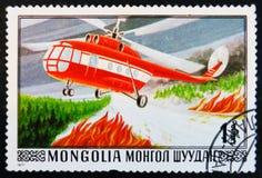 der Beitragsstempel, der in Mongolei gedruckt wird, zeigt feuerbekämpfenden Hubschrauber, circa 1977 Stockbild
