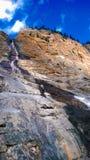 Der Berg, der über Sonnenlicht- und Wolkenkaskadenquellwasser rollt, fallen Stockbild
