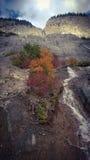 Der Berg, der über Sonnenlicht- und Wolkenkaskadenquellwasser rollt, fallen Lizenzfreies Stockbild