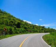 Der Berg, der Himmel, Wolken und die Kurve der Straße Lizenzfreie Stockfotos
