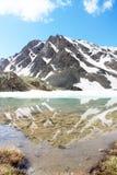 Der Berg mit Schnee-mit einer Kappe bedeckten Spitzen wird im eisigen See reflektiert Stockfotos