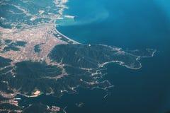 Der Berg und der Ozean, Ansicht vom Flugzeugfenster stockfotografie