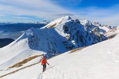 Der Bergsteiger, der auf die Oberseite der Kante geht Stockfotos