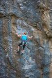 Der Bergsteiger bildet aus, um den Felsen zu klettern stockfotos