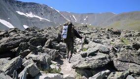 Der Bergsteiger klettert langsam herauf die Klippen stock footage