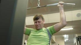 Der ?berladene Mann teilt den oberen Block in der Turnhalle Eignung Gesunder Lebensstil stock video footage