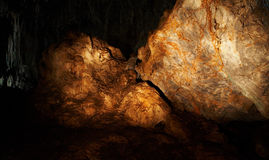 Der bernsteinfarbige Felsen in einer Höhle Stockbild