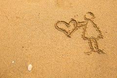 In der Beschaffenheit des Sandes: Mädchen, das ein großes Herz hält Liebe Stockfotos