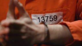 Der besorgte Gefangene, der Finger, Bedauern über das Begehen des Verbrechens knetet, übergibt Nahaufnahme stock video footage