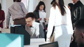 Der betonte und müde junge kaukasische Geschäftsmannmanager, der im beschäftigten modernen Büro arbeitet, Frau setzt Dokumente au stock video