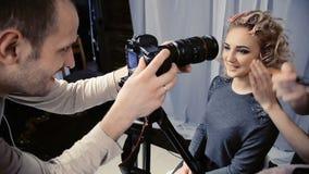 Der Betreiber entfernt das Kameramake-up auf dem Mädchen stock video footage