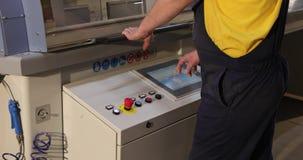 Der Betreiber lässt eine automatisierte Linie, die Betreiberarbeiten nahe einem modernen Maschinenmonitor, die automatisierte Ste stock video footage