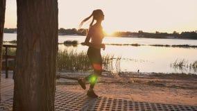 Der Betrieb zwei junger Frau im Park über Brücke und Stoppen nahe Fluss, während des Sonnenuntergangs, Gewichtsverlust, schöne An stock video footage