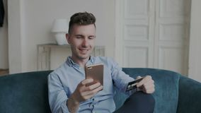 Der bezaubernde und reizend junge Mann, der online kauft, benutzt ein Telefon und eine Kreditkarte auf Sofa zu Hause Er stellt si stock video