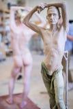 Der Bildhauer sculpts eine Mann ` s Skulptur von der Natur Vertikaler Rahmen Lizenzfreie Stockfotos