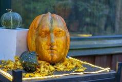 Der bildhauerische Kopf wird von einem orange Kürbis geschnitzt lizenzfreie stockfotografie
