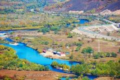 Der blaue Fluss und eine gewundene Straße Stockbilder