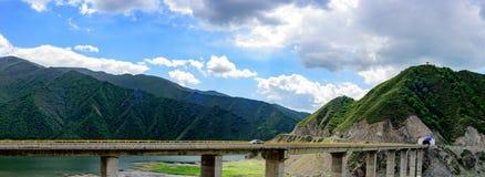 Der blaue Himmel, die weißen Wolken, die grünen Berge und der See wässern, die Autos, die das Verjagen des Tunnels auf den Viaduk Lizenzfreie Stockfotos