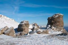Der blaue Himmel und die Steine im Schnee auf einem Leid Lizenzfreie Stockfotos