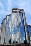 Der blaue Himmel und die Wolken werden in den Spiegelfenstern eines modernen Hotels des Glases und des konkreten, sonnigen Tages, stockfotografie
