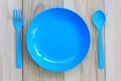 Der blaue Teller, der auf Bretterboden leer ist und haben Kopienraum lizenzfreies stockbild